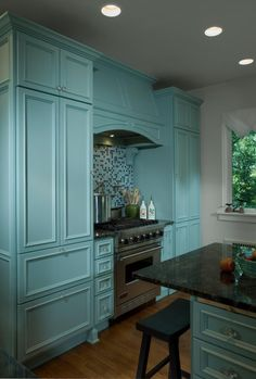 Interior designer Karen Garlanger out of St. Joseph, Michigan was inspired by the cloud color in the granite when she chose Benjamin Moore's Wythe Blue for the custom cabinets.