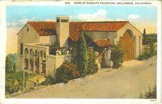 Rudolph Valentino' Whitley Heights postcard. The image features a color-tinted exterior shot of the front and side of Valentino's hillside Spanish house originally located at 6776 Wedgewood Place in the Whitley Heights area of Hollywood, CA. The home features an attached garage with thick wooden doors and a walled interior front courtyard. Other beautiful homes in the area can be seen in the distance, the majority of which were demolished along with Valentino's house.