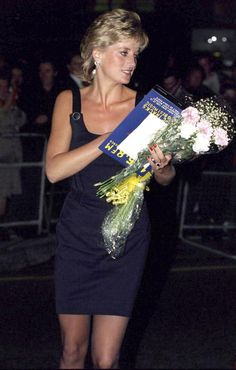 Princess Diana carries the film program and bunches of flowers as she leaves…