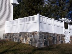 white vinyl with framed top victorian pickets mounted to rock wall