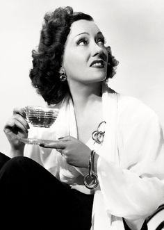 Gloria Swanson (1899-1983) with a cup of coffee.