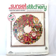 Sunset Stitchery Christmas Wreath Fantasy, Christmas Keepsake, 3 Dimensional Wreath, Christmas Craft Decor Kit, Wall Decor  Description - This festive Christmas wreath features lots and lots of toys and ornaments and Santa!  Measurements - Finished Size 16 x 16 frame  Condition - The needle which was placed in the fabric in the 1970s has begun to rust. Using a new needle, the rust will be covered with the thread when completed.  Materials - Printed design on 20 x 20 50% polyester/50% cotton…