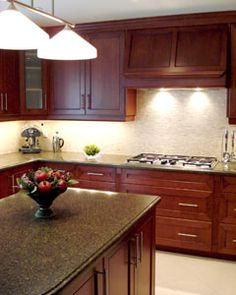 add a glass and stone backsplash, freestanding stove or slidein, laminate to match the granite on the island on the L, wood floor to coordinate with the cabinets