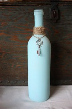 Matte blue painted wine bottle. Has a silver skeleton key dangling from twine wrapped around the neck. How easy would this be? With various sized bottles? Love it. Thinking seafoam green and various shades.