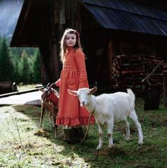 This is a photo of a young girl holding two goats by rope. I find it to be glorious, because of the light and the exposure. I also like the rugged building in the background.