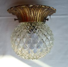 A perforated white ceramic shade hangs from a 12 brass rod and