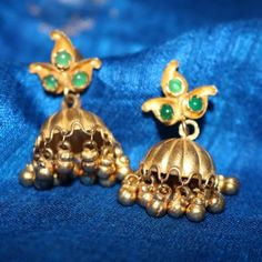 Product Details: Base Material - 92.5 Carat Pure Silver with Gold Plating Technique - Handcrafted Product Type - Temple Jewellery  Design - Jhumka Stones Colour - Green Length - 5 cm  Width - 3 cm  Care Instructions - Avoid Contact with Perfumes and Water  Contact No - +91 8095752326  E-Mail - contactus@madhurya.com   Also available in Pure Gold* Shipping Worldwide