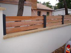 Clôture mixte aluminium et bois, avec lames horizontales. Fixée sur muret par scellement ou par platines