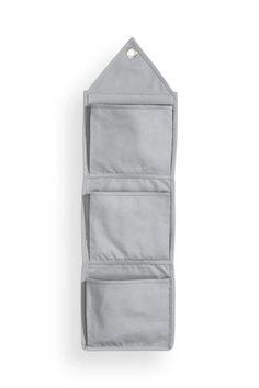 En vägghängd förvaring i canvas med tre fickor. Öljett upptill för enkel upphängning. Storlek 27x95 cm.