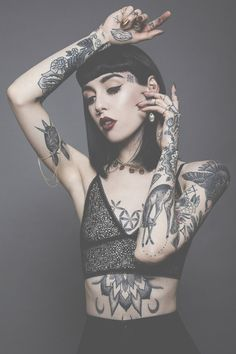 Tattooed lady in crop top and tight black pants