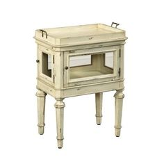 This small side table is a great piece for showing off collector items or a few favorite books. The case features two glass doors and a lift-off tray with brass-finished handles, and four hexagonally turned legs. The casual antique white painted finishwith distressing completes the look.