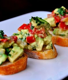 Guacamole Bruschetta - Ingredients: 1/2 loaf French bread 1 clove garlic 2 Tablespoons olive oil 2 tomatoes, medium chopped 2 avocados, medium chopped 1/3 cup finely chopped onion 1/4 cup chopped cilantro 2 Tablespoons freshly squeezed lime juice 1/2 teaspoon salt 1/4 teaspoon pepper