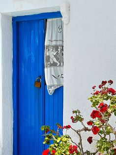 Blue wooden door and red flowers. Plaka, Milos island, Cyclades, Greece