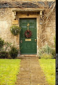 Stone path to green front door with Christmas wreath on English country house