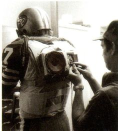 1980 49ers QB wore speakers on his back to amplify his play calling  In 1980, 49ers quarterback Steve DeBerg got laryngitis and couldn't call plays loud enough for his teammates to hear him. So they invented a contraption with speakers that strapped to his back connected to a microphone in his helmet.