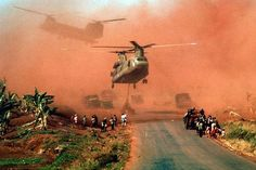 Two Chinook helicopters hover above a road as they assist in evacuating supplies and soldiers of the South Vietnamese (ARVN) 18th Division and their families from Xuan Loc, Vietnam, mid April, 1975. The road is likely Highway 1. April 15, 1975   Photo credit: Lizenz