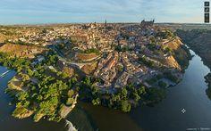 Panorámica aérea de Toledo en una mañana de agosto cuando los primeros rayos de sol revelan volúmenes y texturas de una ciudad rodeada por el rio Tajo cuya historia se remonta a la edad de bronce.