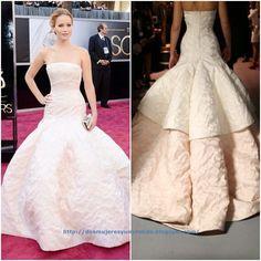 De los Oscar: Jennifer Lawrence. Con un impresionante vestido rosa palo de seda escote bustier de Dior Alta Costura primavera 2013. El clutch de Roger Vivier y las joyas de Chopard.