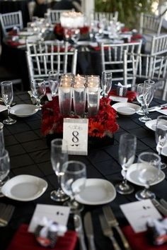 square center piece with red Gerber daises, silvery candle holders with floating votives in the center. Silver Chiavari Chairs