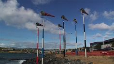 Phil Dadson: Akau Tangi consists of 10 stripe painted poles, each supporting a kinetic conical element that vanes with wind direction and spins on its axis according to wind speed, producing dynamo-operated LED lighting that brightens or dulls according to wind speed. Aeolian flute and whistle tones are produced from each of the 10 sculptures by wind-driven flutes at the cowl end of each form. Wind Direction, Wind Sculptures, Flutes, Wind Turbine, Cowl, Artists, Led, Lighting, Outdoor Decor