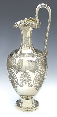 A VICTORIAN SILVER WINE JUG, JOSEPH & ALBERT SAVORY, LONDON 1853 of ewer form with everted triform spout with a lobed rim flanked by two mask heads and a high handle terminating in a female head, the neck and sides engraved with stylised palmettes