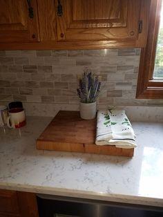Oak cabinets with Lyra quartz and marble backsplash.
