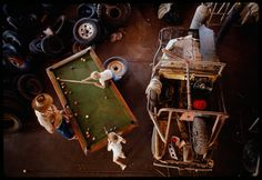 A rancher plays pool with his children in their garage, Western Australia, May 1989.Photograph by Sam Abell, National Geographic