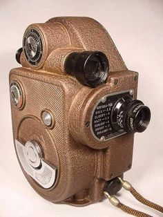 BROWN REVERE MOVIE CAMERA Vintage Old Art Deco Antique Classic BROWN REVERE EIGHT MOVIE CAMERA  This camera was made by Revere Camera Company of Chicago, Illinois in the 1940's.  Notice the wonderful Art Deco styling of the camera, the beautiful shape and designs, and the contrast of the brown and silver of the camera.  The viewfinder is a black viewing tube built into the top of the camera. There is a focusing setting on the side of it. Notice the metal exposure guide built into the other…