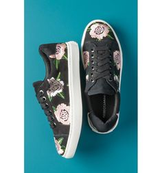 Shimmering embroidered flowers add romantic flourish to a street-smart leather sneaker grounded by a sporty bumper sole.