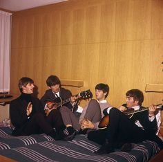 The Beatles pictured together rehearsing songs in their hotel room in Stockholm during their autumn tour of Sweden in 1963