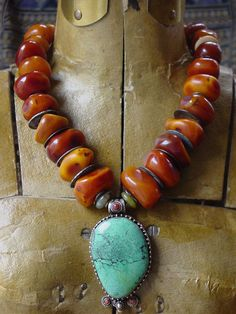 by Helena Nelson-Reed | Necklace;  handmade vintage amber - resin (not fossilized or Baltic amber) and antique I Ching coins serve as spacers. The I Ching coins are authentic, worn, and naturally aged, the varying degrees of teal patina. The pendant is a contemporary Tibetan silver, turquoise and coral piece | SOLD