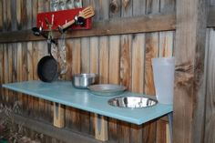 mud kitchen -- i like the idea of creating a sink by cutting a hole into a board and putting a metal bowl into it