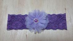 Faixa de renda com elastano roxa, com flor lilás de organza cristal. Miolo com strass e meia pérola roxa.