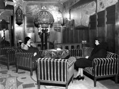 """1940's. View of the lobby of Tuschinski Theater in Amsterdam. The Tuschinski movie theater was acquired by Abraham Icek Tuschinski in 1921 at a cost of 4 million guilders. The interior and exterior are a spectacular mix of styles: Amsterdam School, Jugendstil, Art Nouveau, Art Deco. When it first opened, the theater contained electro-technical features, then considered revolutionary. During the World War II the theatre was given the (non-Jewish) name """"Tivoli"""". #amsterdam #1940 #Tuschinski"""