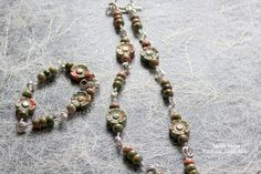 Unakiitti on kukat ovat ihanasti kaiverretut ja saivat kaverikseen rondelleita samasta materiaalista. Lisänä hippasen hopeaa. Väri on oliivinvihreää ja lohenpunaista. Kaulakoru ja rannekoru käyttöön kesämekon kanssa :)
