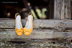 Love the contradiction of bright yellow heels on the worn and rustic barn railing.