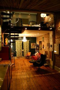 The second floor of this loft type apartment is open to the first floor, because there is no wall there it makes the room seem more connected as well as larger. the spiral staircase also adds to the room as a decorative point more than a normal bulky staircase would.