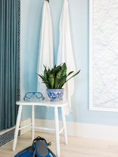 The soft hue of the French blue painted walls is the perfect backdrop for white accessories like towels and a white painted wood stool. | HGTV® Dream Home 2016