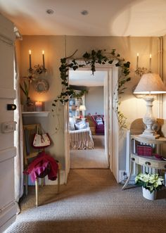 Candlelight and trailing garland in festive entrance hall with seagrass carpet and victorian wall sconces
