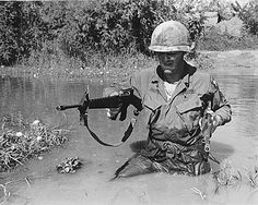 A 101st Airborne Division Soldier wades through mud and water during a mission in Vietnam.