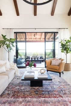For your solarium; love the deep red vintage rug with mostly white and tan furnishings and the exposed beams on the ceiling.