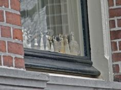 Wedding cake toppers between window panes in Amsterdam. No idea why they do it though...
