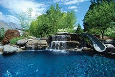 A rock waterfall and a slide definitely puts this pool at the top of our dream backyard necessities!