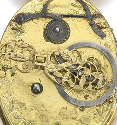 Nicholas Vallin  A SIGNIFICANT ELIZABETHAN EARLY GILT-METAL OVAL VERGE WATCH CIRCA 1600  - gilt dial with Roman numerals and half hour star-shaped markers, silver touch pins within chapter ring marking hours, single arrow hour hand, central engraving of seated cherub beside an hourglass with an elbow resting upon a skull - length including pendant, 67 x 42mm - sotheby's