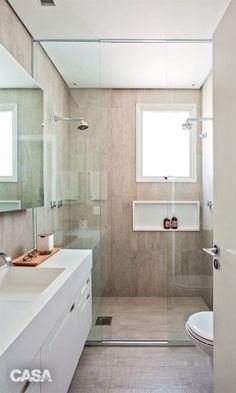 No banheiro, cobrir piso e paredes com o mesmo porcelanato do restante do apartamento (Portland Line Relevo, da Portobello) garante unidade visual. Metais da Deca. 60 x 120 x 1,1 cm https://www.portobello.com.br/produtos/porcelanato-revestimento-ceramico/concretissyma/portland-line-relevo-60X120-nat