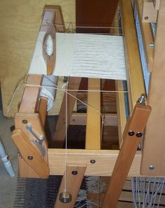 TEMPLES INSTALLED ON THE LOOM - NOTE THAT THE KNOTTED CORD HANGING DOWN IS THE MEASURING STRING NOT PART OF THE TEMPLE