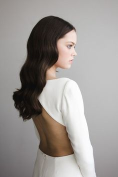 this minimal and simple bridal hairstyle with soft waves is perfect for a minimal and classic wedding, the bridal dress is made of a stiff white fabric and has a open back   #bridaldress #minimalwedding #bridalhair