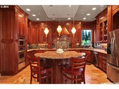 Rich cherry wood cabinets with light countertops and light floor