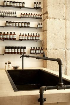 Aesop. Natural Materials, simple light shelving systems, tonal space, a central fixture with expressed  tapwork.
