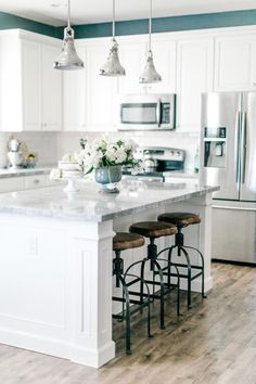 Traditional meets contemporary kitchen with custom built kitchen island with gray marble counter tops, industrial farmhouse-style stools, white shaker cabinets, silver industrial pendant lights, chrome appliances, white beveled edge subway tile backsplash and glossy oak hardwood floors.